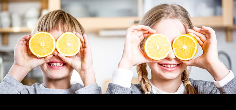 деца си играат со портокали